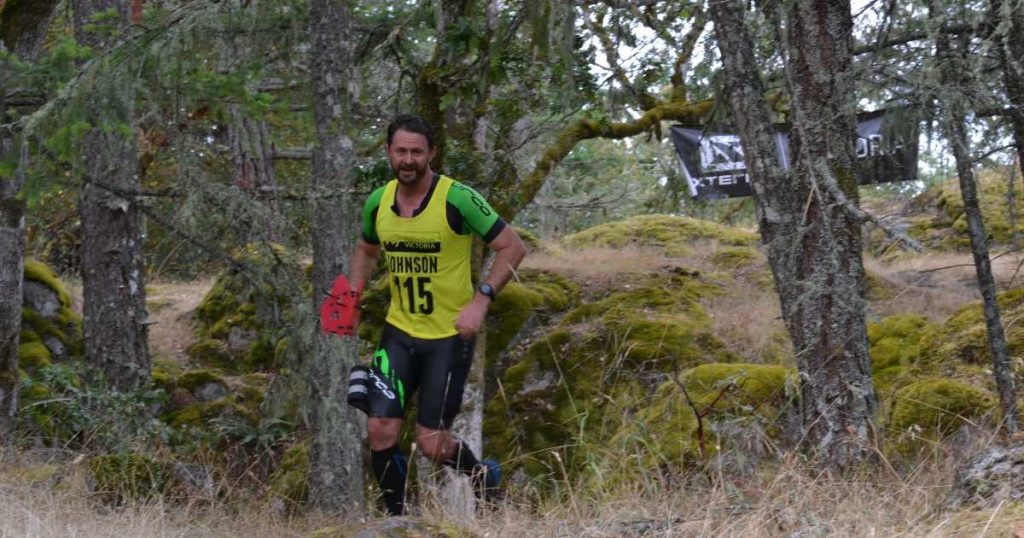 A man runs over the top of a hill in a forest smiling and wearing wet clothes.